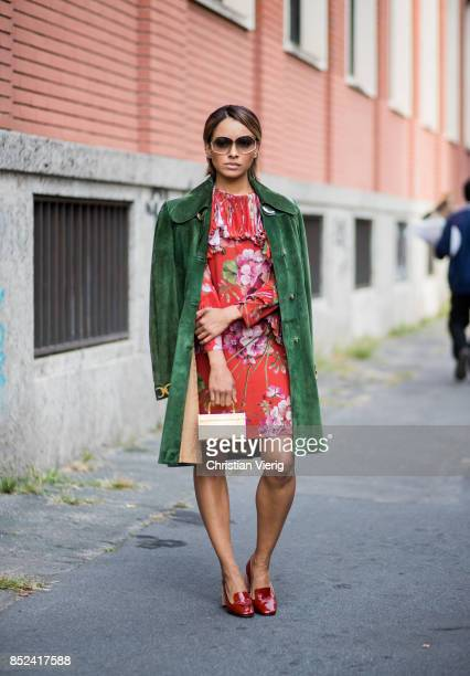 Kat Graham wearing red Gucci dress with floral prints green Gucci coat golden mini bag red heeled shoes sunglasses is seen during Milan Fashion Week...