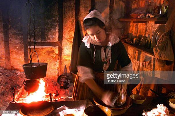 Kat Zak who plays Pilgrim Priscilla Alden glows in the fire inside her home at Plimoth Plantation as she prepares a Thanksgiving meal The Plantation...