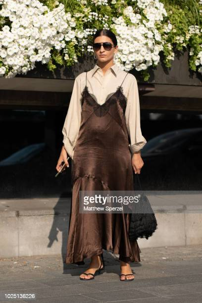 Katarina Petrovic is seen on the street during Fashion Week Stockholm SS19 wearing brown silk dress with black fringe and taupe buttondown shirt with...