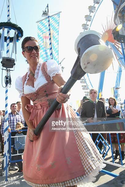 Katarina Witt enjoys the high striker during the BMW Wiesn Sport Stammtisch Oktoberfest 2013 at Kaefers Wiesn Schaenke Theresienwiese on September 24...