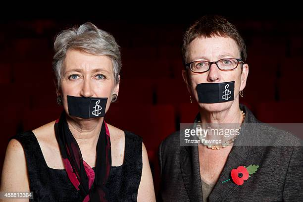 Kate Allen Director of Amnesty International UK and Lindsey Hilsum tape their mouths closed to show solidarity with Al Jazeera journalists jailed in...