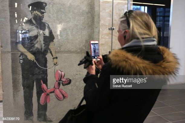 TORONTO ON FEBRUARY 16 Kate Bahen takes a photo of the Banksy that was saved from a Toronto building Menkes development has 'rescued' a work...