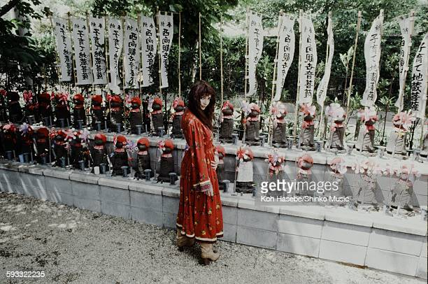 Kate Bush in front of stone statue of Jizo in a temple in Tokyo June 1978