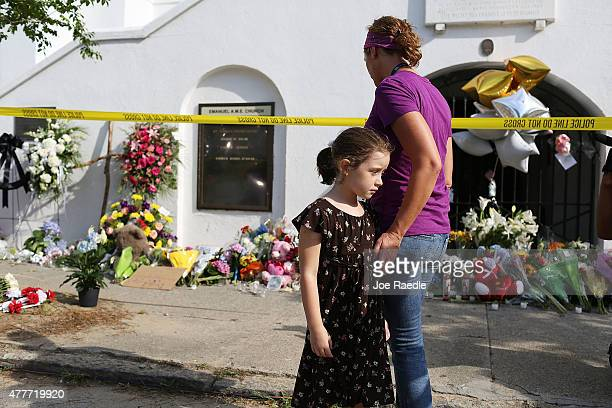 Kate Daby and her daughter, Adeline Daby pay their respects in front of Emanuel African Methodist Episcopal Church after a mass shooting at the...