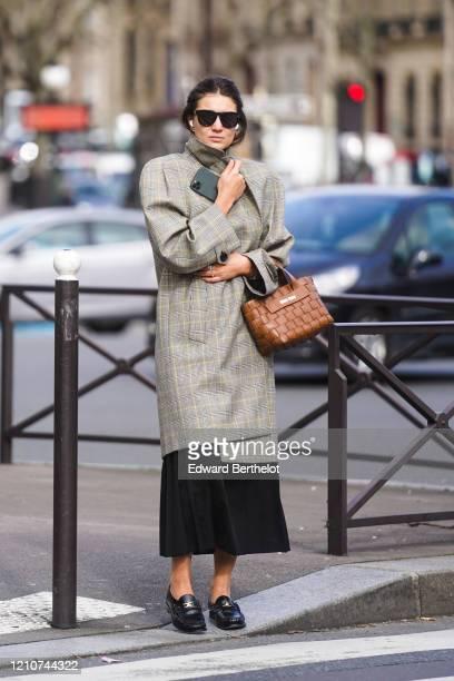 Kate Darma wears sunglasses, a checked pattern oversized blazer long jacket with shoulder pads, a Miu Miu brown leather bag, a black dress, black...