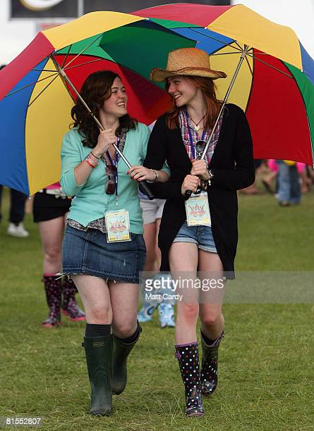 Kate Eyres and Robyn Linsday laugh as they try out their new umbrellas after hearing that heavy rain is forecast for the weekend at the Isle of Wight...