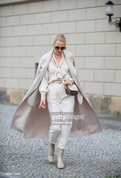 Kate Gelinsky is seen wearing belt and bag Aigner, creme white coat Hallhuber, Mango pants, Arket blouse, Karen Walker sunglasses, Zara boots during...