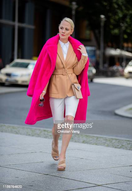 Kate Gelinsky is seen wearing total look Marc Cain pink teddy coat, white shorts, brown blazer, brown bag, sandals, white button shirt during...