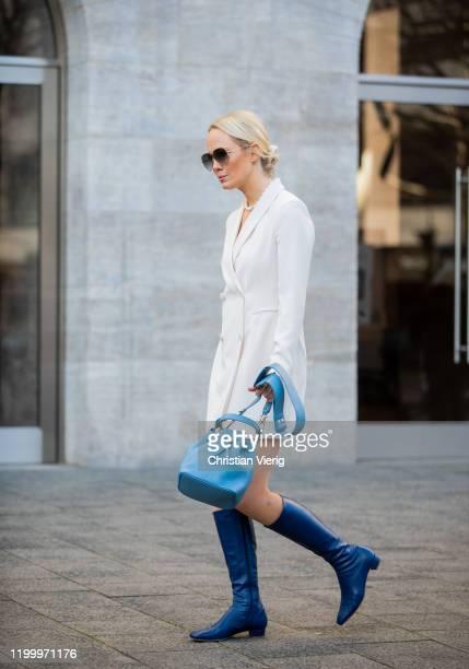 Kate Gelinsky seen wearing blue Aigner bag, creme white blazer Hallhuber, Victoria Beckham sunglasses, by Far boots during the Berlin Fashion Week...