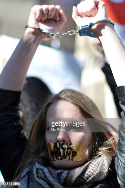 Kate Hamberer of NY holds up her hands in cuffs as she stands with other protestors during Presidents Day February 20th 2017 To protest the...