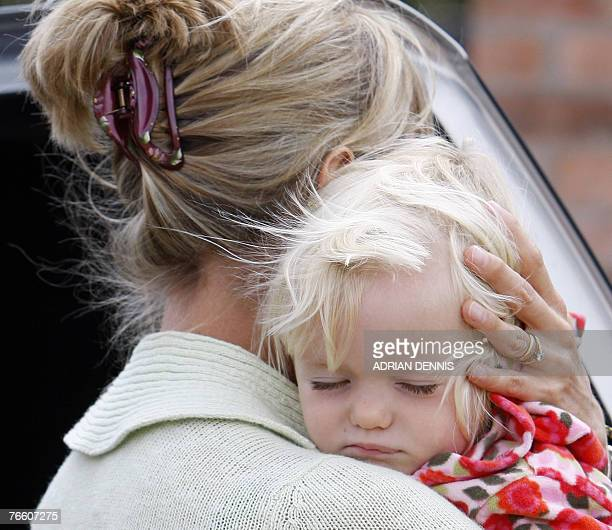 Kate McCann carries one of her twins Amelie into the house 09 September 2007 after arriving back at the family home in Rothley Leicestershire The...