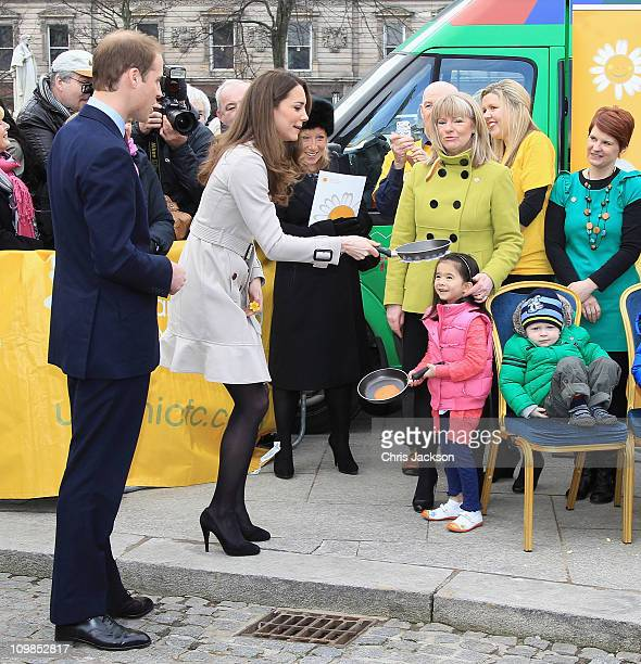 Kate Middleton tosses a pancake as Prince William looks on during a visit to City Hall on March 8 2011 in Belfast Northern Ireland The Royal Couple...