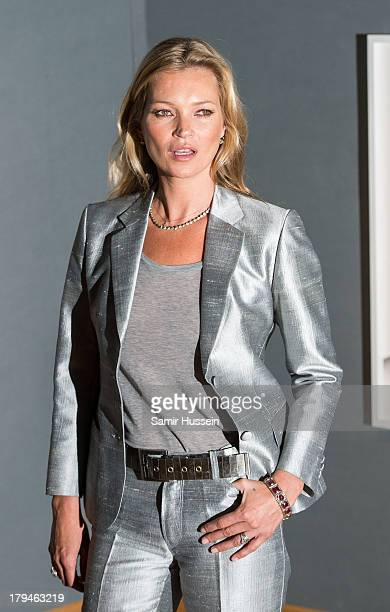 Kate Moss poses at a photocall ahead of the Kate Moss The Collection auction which sees various artworks of the model curated by Gert Elfering go...