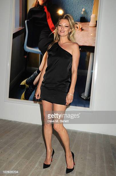 Kate Moss poses in front of one of her portraits at the 'Mario Testino: Kate Who?' private viewing at Phillips de Pury & Company on July 5, 2010 in...