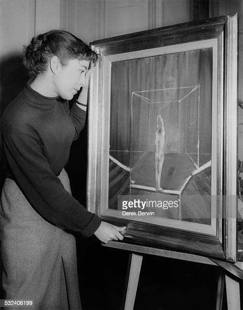 Kate Munday an employee at the Institute of Contemporary Arts in Piccadilly London places a Francis Bacon painting on a stand prior to an exhibition...