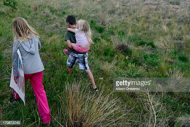 Kate Murdock waks wtih her brother Dallin as he carries little sister Lea to greet fire crews upon their return to the incident command post