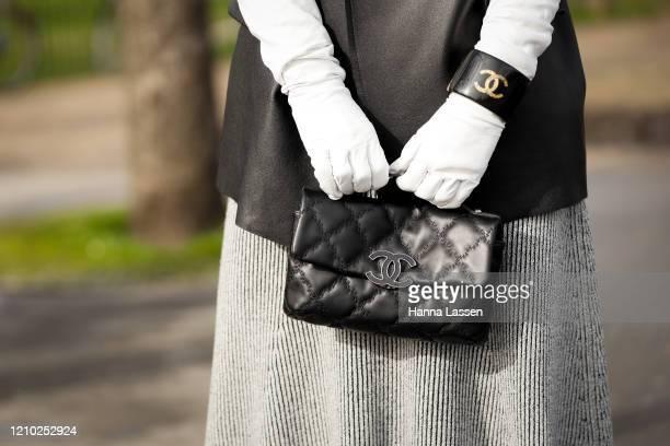 Kate Tik, bag detail, wearing Chanel black oversized leather jacket, grey maxi dress, chanel bag, white gloves, bangle and black boots outside Paris...