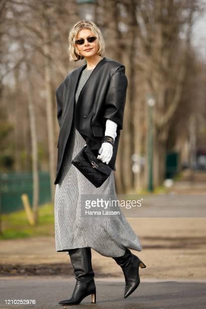 Kate Tik wearing Chanel black oversized leather jacket, grey maxi dress, chanel bag, white gloves, bangle and black boots outside Paris Fashion Week...