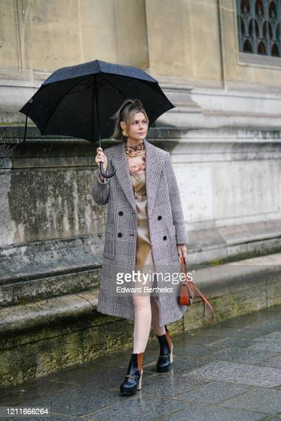 Kate Tik wears a khaki leather dress, a golden necklace, a gray checked long coat, a brown leather bag, black leather boots, earrings, during Paris...