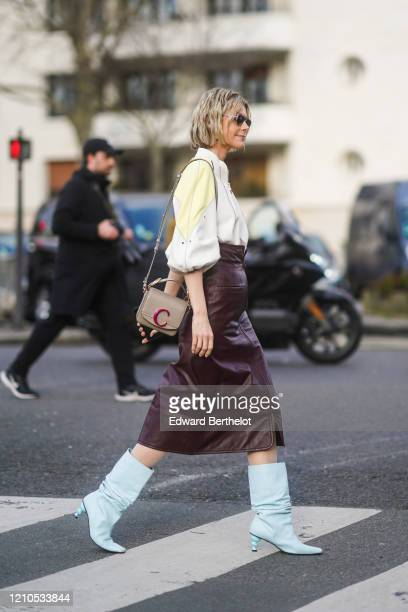 Kate Tik wears a white and yellow shirt with puff sleeves, a Chloe bag, a burgundy leather skirt, pale blue pointy boots, outside Lacoste, during...