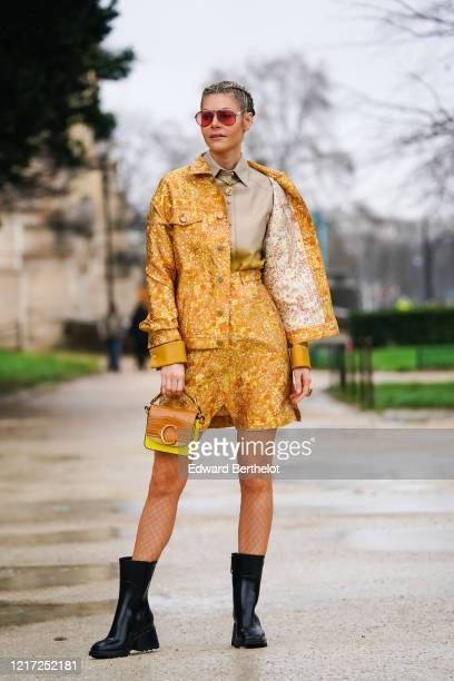Kate Tik wears aviator sunglasses, a gray shirt, a yellow and orange floral print jacket, shorts, fishnet tights, a brown and yellow crocodile...