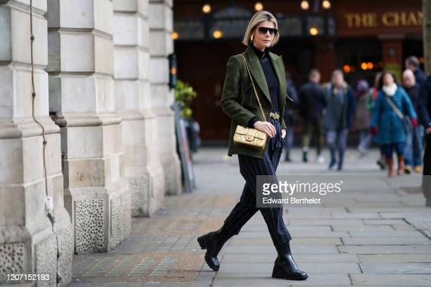 Kate Tik wears sunglasses, a green jacket with fringes, a golden Chanel small bag, a black top, striped navy blue pants, black shiny boots, during...