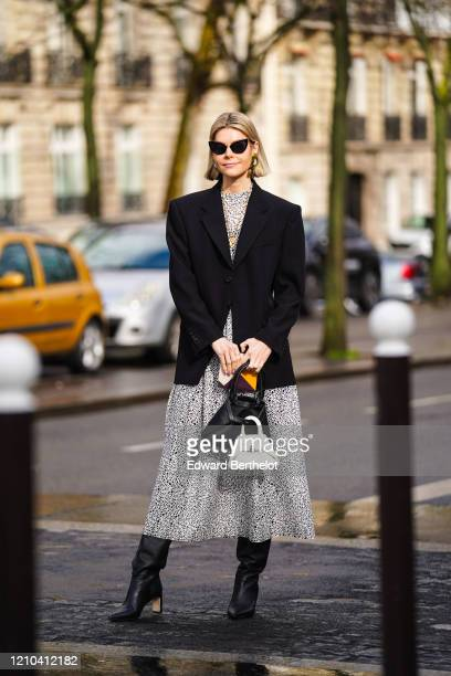 Kate Tik wears sunglasses, earrings, necklaces, a white and black mesh dress, a black jacket, a black bag and a white one, black pointy heeled boots,...