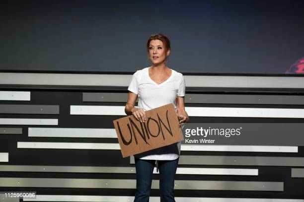 Kate Walsh speaks while holding a sign that reads 'UNION' onstage during The 21st CDGA at The Beverly Hilton Hotel on February 19 2019 in Beverly...