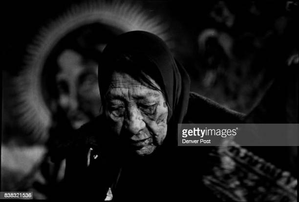 Kate wife of the Oglala Sioux chief Fools Crow sit in front of a tapestry of Jesus on her farmhouse sofa She bows her head as her husband blesses...