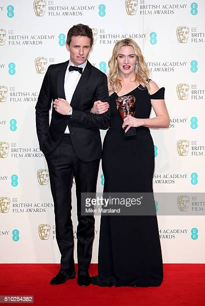 Kate Winslet poses with the award for Supporting Actress for 'Steve Jobs' and presenter Eddie Redmayne in the winners room at the EE British Academy...