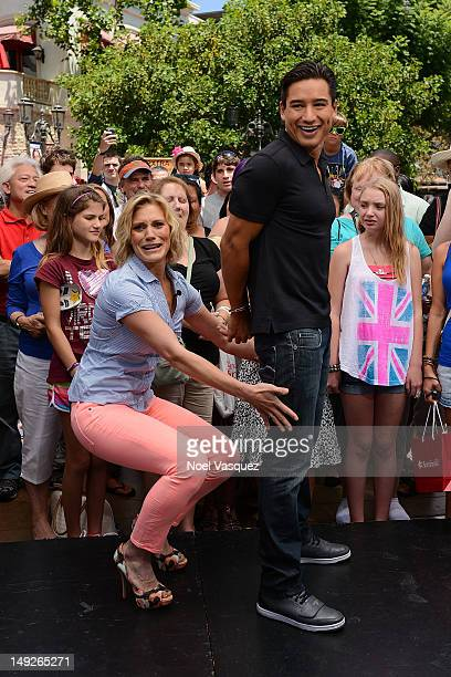 Katee Sackoff attempts to place handcuffs on Mario Lopez at 'Extra' at The Grove on July 25 2012 in Los Angeles California