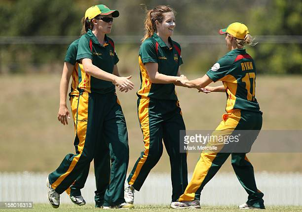 Katelyn Fryett and Carly Ryan of the Roar celebrate taking the wicket of Alyssa Healy of the Brakers during the women's Twenty20 match between the...