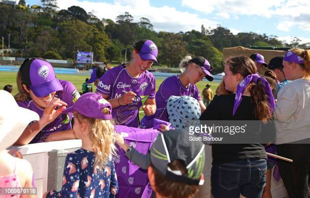 Katelyn Fryett of the Hurricanes signs autographs for supporters in the crowd during the Women's Big Bash League match between the Hobart Hurricanes...
