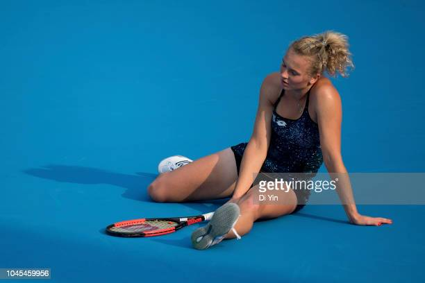 Katerina Siniakova of the Czech Republic sits injured during her women's third round match against Kiki Bertens of Netherlands of 2018 China Open at...