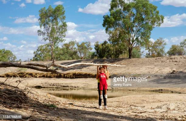 Kathalka Whyman holds up Kaakuru Whyman on the dry bed of the Darling Barka river on March 04 2019 in Wilcannia Australia The Barkandji people...