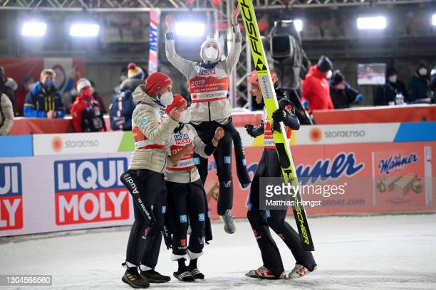Katharina Althaus, Markus Eisenbichler, Anna Rupprecht and Karl Geiger of Germany celebrate as they are announced winners during the Ski Jumping...