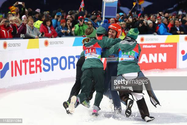 Katharina Althaus of Germany celebrates with team mates Ramona Straub Juliane Seyfarth and Carina Vogt after winning the HS109 women's ski jumping...