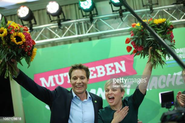 Katharina Schulze and Ludwig Hartmann colead candidates of the German Greens Party hold up flowers to supporters at the Bavarian state parliament...