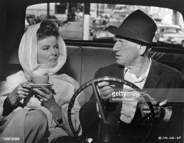 Katharine Hepburn and Spencer Tracy sitting in a car together enjoying a snack in a scene from the film 'Guess Who's Coming to Dinner', 1967.
