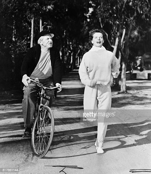 Katharine Hepburn in the role of an allaround sports champ in a scene from the forthcoming film Pat and Mike Spencer Tracy is shown riding along side...