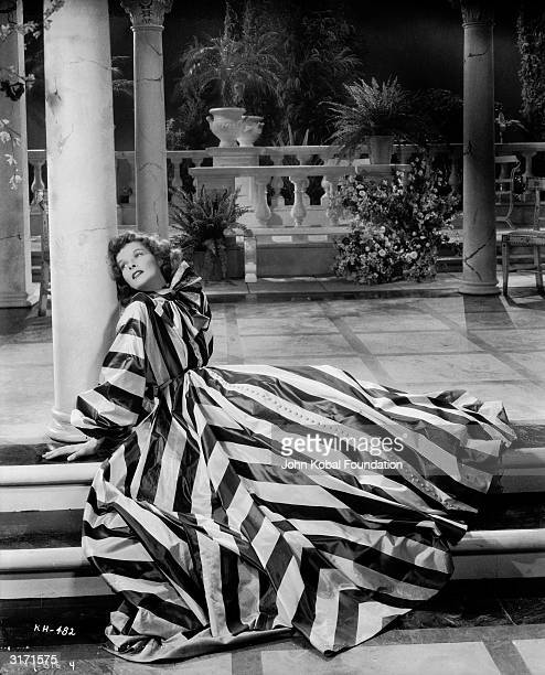 Katharine Hepburn reclines on the verandah in a bold striped gown with a bow collar in this scene from 'Break of Hearts' directed by Philip Moeller...