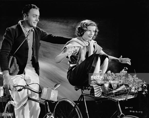 Katharine Hepburn shows off her cycling ability to Charles Boyer in a romantic scene from 'Break of Hearts' directed by Philip Moeller