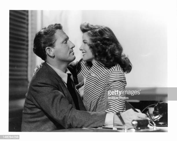 Katharine Hepburn sitting on Spencer Tracy's lap in his office in a scene from the film 'Woman Of The Year', 1942.