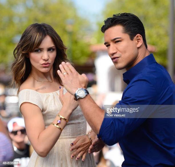 Katharine McPhee and Mario Lopez pose together at 'Extra' at Universal Studios Hollywood on April 14 2014 in Universal City California