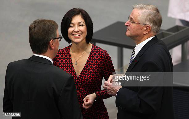 Katherina Reiche of the Christian Democratic Union talks with two unidentified men as she attends the constitutional meeting at the Bundestag on...