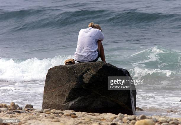 Katherine Batty a longtime summer resident of the Vineyard sits on a rock on Moshop Beach in Aquinnah near the area where debris from John F Kennedy...