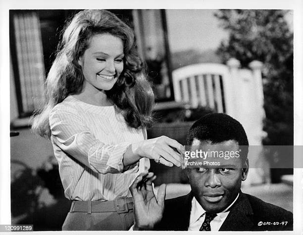 Katherine Houghton puts flower Sidney Poitier's hair in a scene from the film 'Guess Who's Coming To Dinner' 1967