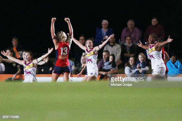 Katherine Smith of the Demons celebrates the win on the final siren as Lions players call for a free kick to have the chance to draw during the round...