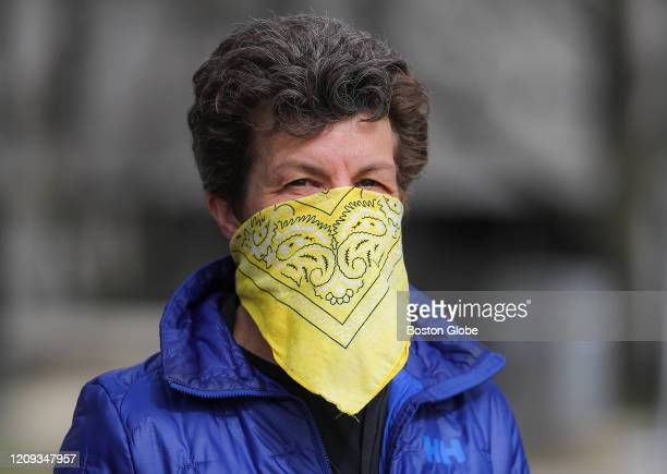 Katherine Sruscott uses a bandana as a makeshift mask as she walks along Memorial Drive in Cambridge on Apr. 5, 2020. The CDC Friday reversed their...