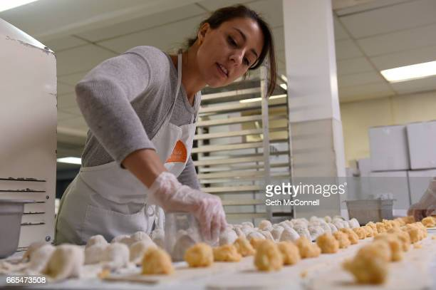 Katherine Yurek uses a measuring cup to make a perfect circular cut around potato and cheese pierogis at a commercial kitchen on April 4 in Denver...